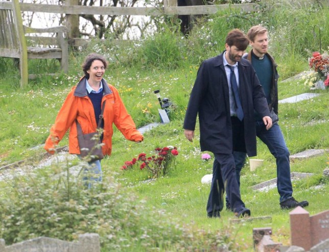L-R, Olivia Colman, David Tennant, and Arthur Darvill,  filming new episodes for series two of TV drama Broadchurch at St Andrew's church, Clevedon, North Somerset.  Series two of surprise hit TV show, Broadchurch, began filming in the seaside town of Clevedon with fans being shown a bit more than they expected. See swns story SWBROAD. Jodie Whitaker, 32, who plays Beth Latimer in the show, was spotted on set with a bigger baby 'bump' as she returns to play the pregnant character in the show. Beth, was the mother of murdered Danny and her suspicions grew throughout the series about who she could and couldn't trust.  Fans were taken on a wild roller coaster ride as she becomes increasingly suspicious of her husband, Mark.  While the character was determined Mark, played by Andrew Buchan, had murdered her son after he couldn't provide an alibi, the series finale later showed it to actually be DS Miller's husband, Joe, played by Matthew Gravelle. Throughout series 1 of the hit show, which swept up three Baftas, Beth was three months pregnant, but this is expected to develop throughout the second series.