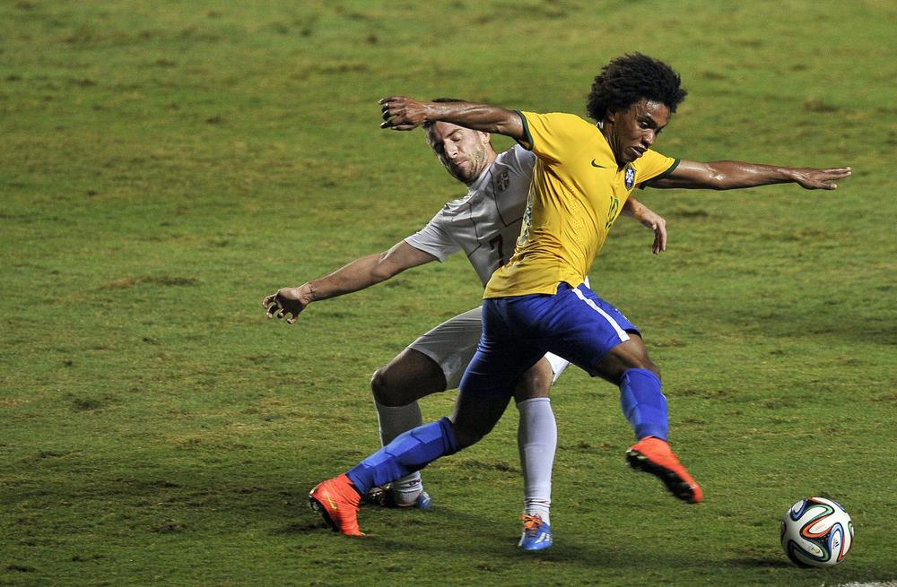 Brazil's Willian (R) vies for the ball with Serbia's Zoran Tosic, during their friendly football match in preparation for the FIFA World Cup Brazil 2014 at Morumbi stadium in Sao Paulo, Brazil on June 06, 2014. AFP PHOTO / Miguel SCHINCARIOL MIGUEL SCHINCARIOL/AFP/Getty Images