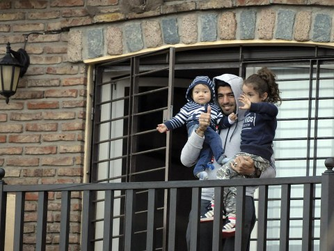 Uruguay fans cheer Luis Suarez as he waves and gives thumbs-up from balcony