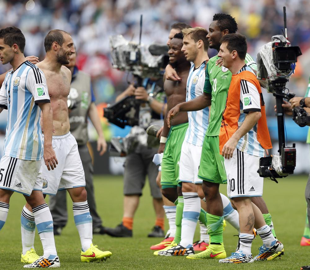 Argentina's Pablo Zabaleta, left, talks to his teammate Lionel Messi, right, and Nigeria's Mikel John Obi, second right, after the group F World Cup soccer match between Nigeria and Argentina at the Estadio Beira-Rio in Porto Alegre, Brazil, Wednesday, June 25, 2014. Argentina won 3-2. (AP Photo/Victor R. Caivano) AP Photo/Victor R. Caivano