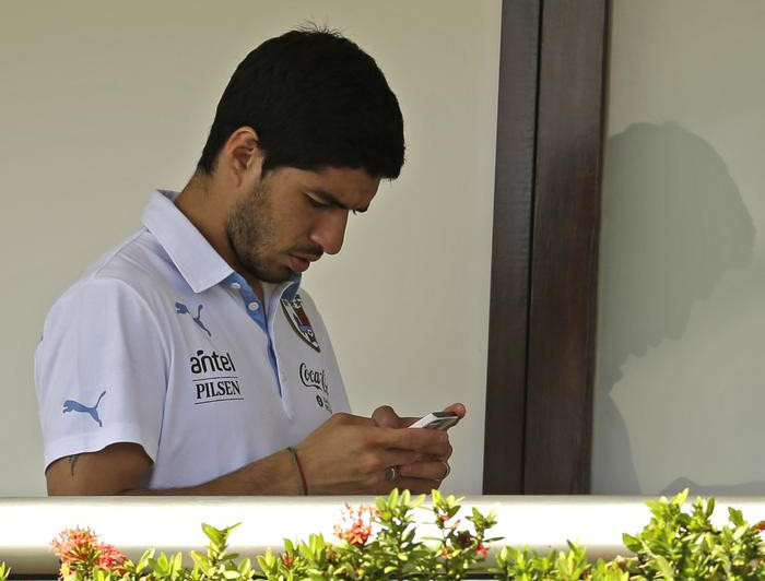 Uruguay's Luis Suarez uses his cell phone at a hotel in Natal, Brazil, Wednesday, June 25, 2014. Suarez bit Italian player Giorgio Chiellini during Uruguay's game with Italy on Tuesday, which could lead to Suarez being kicked out of the World Cup. (AP Photo/Hassan Ammar) AP Photo/Hassan Ammar