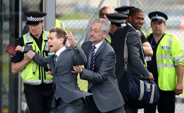 England's Comedian Lee Nelson is taken away by security at Luton Airport, Luton. PRESS ASSOCIATION Photo. Picture date: Sunday June 1, 2014. See PA Story SOCCER England. Photo credit should read: Stephen Pond/PA Wire.