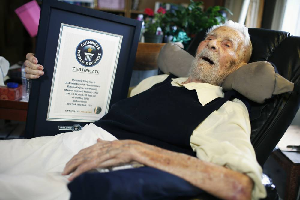 111-year-old Alexander Imich holds a Guinness World Records certificate recognizing him as the world's oldest living man during an interview with Reuters at his home on New York City's upper west side, May 9, 2014. Dr. Imich, who holds a Ph.d in Zoology, was born in Poland on February 4, 1903, fled Poland when the Nazis took over in 1939, survived a slave labor camp in Russia and moved to the United States in 1951 where he became an author on parapsychology.  REUTERS/Mike Segar  (UNITED STATES - Tags: SOCIETY) - RTR3OIBH