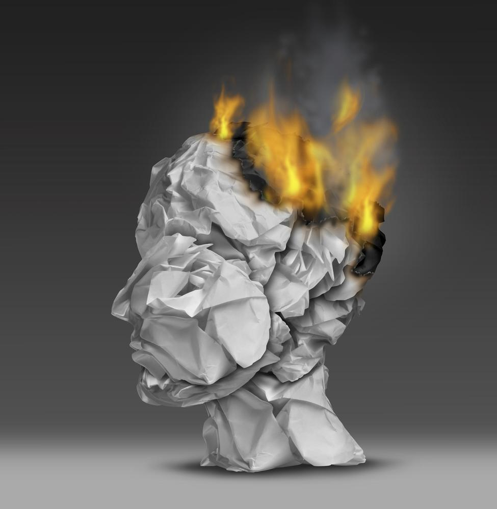 Headache and mental illness concept as a group of crumpled office paper shaped as a human head that is on fire burning away at the brain as a symbol and medical metaphor for emotional stress at work or degenerative dementia disease as alzheimers. wildpixel/wildpixel