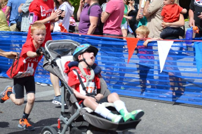 PIC FROM CATERS NEWS - (PICTURED: NOAH PUSHING LUCAS ON HIS ONE MILE RUN) - An inspirational eight year old completed a triathlon and carried his severely disabled brother the whole way. We¿Äôve all head the song ¿ÄúHe ain¿Äôt heavy, he¿Äôs my brother¿Ä, but Noah Aldrich took that to heart by pushing, pulling and pedalling his six-year-old brother Lucas along the course. Lucas was born with a rare brain condition, lissencephaly, which means he is unable to walk, talk or eat by himself. But that didn¿Äôt stop his big brother Noah from signing him up for a triathlon organised by their local YMCA in Boise, Idaho, USA. The amazing Aldrich brothers completed the course in just over 54 minutes with Noah pushing his baby brother over the finishing line in a buggy after a one mile run. SEE CATERS COPY.