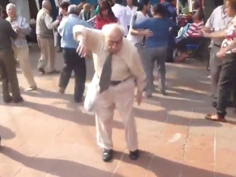 Old man throws down walking sticks and dances at street party