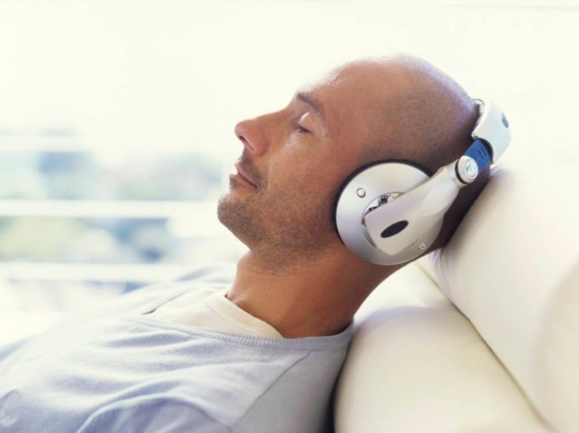 Man sits back and relaxes whilst listening to music through headphones. headsets earphones MEN PERSONAL STEREO POSED BY MODELS RELAXATION rights managed