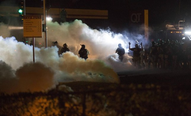 Riot police clear a street with smoke bombs while clashing with demonstrators in Ferguson, Missouri August 13, 2014. Police in Ferguson fired several rounds of tear gas to disperse protesters late on Wednesday, on the fourth night of demonstrations over the fatal shooting last weekend of an unarmed black teenager Michael Brown, 18, by a police officer on Saturday after what police said was a struggle with a gun in a police car. A witness in the case told local media that Brown had raised his arms to police to show that he was unarmed before being killed. REUTERS/Mario Anzuoni (UNITED STATES - Tags: CRIME LAW CIVIL UNREST) Mario Anzuoni/Reuters