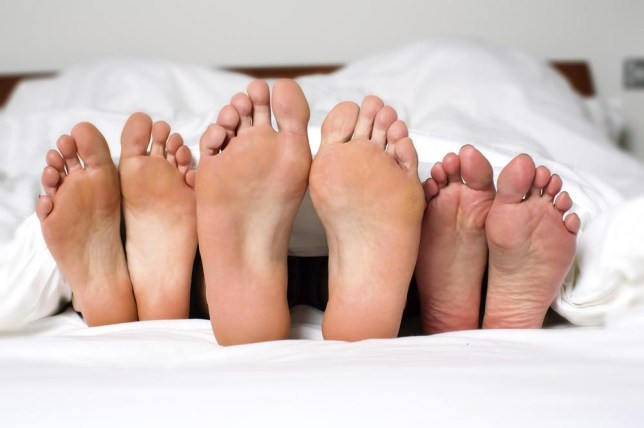 Humorous image of the bare feet of a man and two women in bed sticking out from under the bedclothes conceptual of a threesome, orgy, swingers or sexual cheating FantasticRabbit/FantasticRabbit