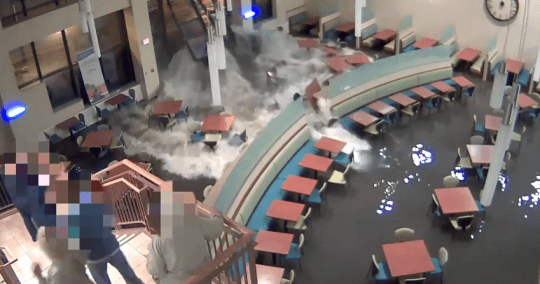Shocking: Onlookers step back as water smashes through the doors of the hospital (Picture: Gary White/YouTube)