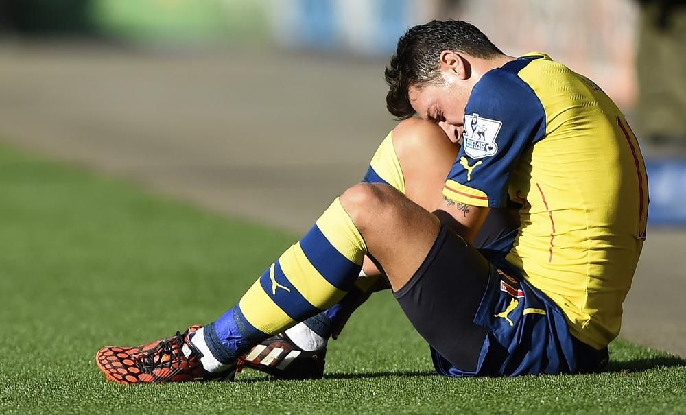 "Arsenal's Mesut Ozil sits injured during their English Premier League soccer match against Leicester City at the King Power Stadium in Leicester, northern England August 31, 2014. REUTERS/Dylan Martinez (BRITAIN - Tags: SPORT SOCCER) NO USE WITH UNAUTHORIZED AUDIO, VIDEO, DATA, FIXTURE LISTS, CLUB/LEAGUE LOGOS OR ""LIVE"" SERVICES. ONLINE IN-MATCH USE LIMITED TO 45 IMAGES, NO VIDEO EMULATION. NO USE IN BETTING, GAMES OR SINGLE CLUB/LEAGUE/PLAYER PUBLICATIONS. FOR EDITORIAL USE ONLY. NOT FOR SALE FOR MARKETING OR ADVERTISING CAMPAIGNS Dylan Martinez/Reuters"