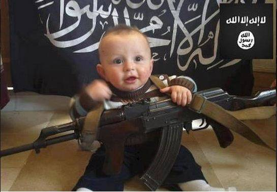 Shocking Isis photos show baby holding an AK-47 and lying on Islamic State flag