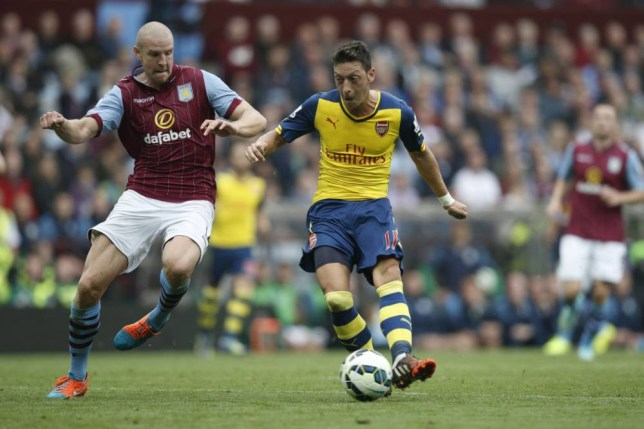Arsenal's German midfielder Mesut Ozil (C) shoots to score the opening goal during the English Premier League football match between Aston Villa and Arsenal at Villa Park in Birmingham, central England on September 20, 2014. AFP PHOTO/ADRIAN DENNIS RESTRICTED TO EDITORIAL USE. No use with unauthorized audio, video, data, fixture lists, club/league logos or live services. Online in-match use limited to 45 images, no video emulation. No use in betting, games or single club/league/player publications.ADRIAN DENNIS/AFP/Getty Images