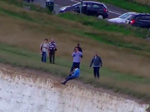 Shocking moment man dangles legs off Beachy Head cliffs for photo