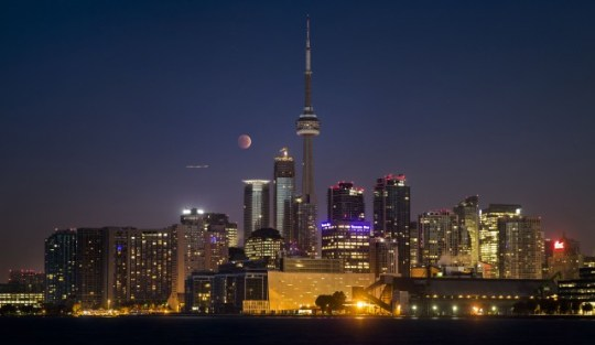 """The moon turns orange during a total lunar eclipse behind the CN Tower and the skyline during moonset in Toronto October 8, 2014. The eclipse is also known as a """"blood moon"""" due to the coppery, reddish color the moon takes as it passes into Earth's shadow. The total eclipse is the second of four over a two-year period that began April 15 and concludes on Sept. 28, 2015. The so-called tetrad is unusual because the full eclipses are visible in all or parts of the United States, according to retired NASA astrophysicist Fred Espenak.   REUTERS/Mark Blinch"""