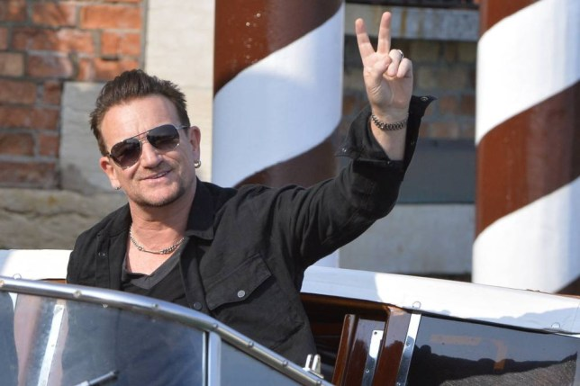 """TO GO WITH AFP STORY """" Bono apologizes for free U2 album on iTunes accounts"""" (FILES) This file picture dated September 27, 2014 shows Irish singer and frontman of U2, Bono, arriving at the Cipriani Hotel in Venice for the wedding of US actor george Clooney with British Amal Alamuddin in Venice. In a video interview hosted on Facebook on October 14, 2014, Bono appeared with the other members of the band to take written questions from fans. Call it a mix of ego, generosity, self-promotion and insecurity. But Bono is sorry for giving away U2's latest album for free on iTunes accounts. AFP PHOTO / ANDREAS SOLAROANDREAS SOLARO/AFP/Getty Images"""