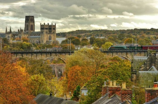 Dated 26/10/2014 AUTUMN IN DURHAM ... Durham Cathedral, one of the finest examples of Norman architecture, rises high above the autumn colour from its prominent position in Durham City as the Pacific A4 60009 Union of South African steam locomotive hauls the 'Jubilee Requiem' carriages from London Kings Cross over Durham Viaduct to Newcastle, which was once a common sight on the East Coast Mainline during the 1950s