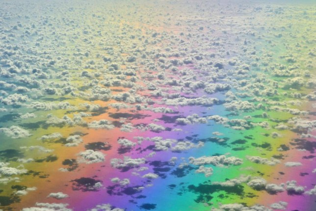 PIC BY CATERS NEWS - (PICTURED: The rainbow below the clouds) - A lucky flier has captured the spectacular moment she flew directly over a RAINBOW. Shocked Melissa Rensen, 51, snapped the kaleidoscope of colour while travelling over the Carribean Sea. But Melissa, from London in Ontario, Canada didnt even realise until she looked at the images later on. She was travelling from North America to Hounduras and spotted an interesting cloud formation below. And after looking back at the shot she noticed the blanket of colour covering the expanse below. SEE CATERS COPY.