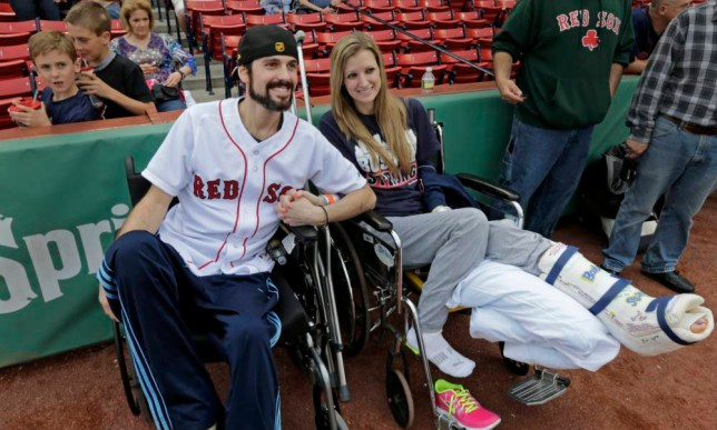 In this Thursday, May 23, 2013 photo, Boston Marathon bombing survivor Pete DiMartino, of Rochester, N.Y., and his girlfriend, Rebekah Gregory, hold hands prior to DiMartino throwing out the ceremonial first pitch before a Red Sox game at Fenway Park in Boston. DiMartino and Gregory were injured in an explosion near the finish line of the Boston Marathon. ¿I don¿t want anybody feeling sorry for me,¿ he said. ¿... I want people to see that this has made me a better person and I want people to become better people through what they see through me.¿ (AP Photo/Charles Krupa)