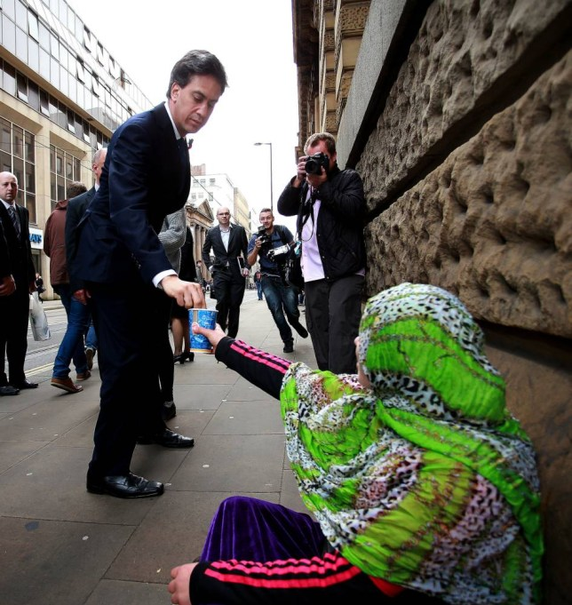 Labour leader Ed Miliband donates money to a lady ahead of a meeting of Labour's English Regional Shadow Cabinet Committee in Manchester to discuss an English Devolution Act. PRESS ASSOCIATION Photo. Picture date: Friday October 31, 2014. See PA story POLITICS Miliband. Photo credit should read: Peter Byrne/PA Wire