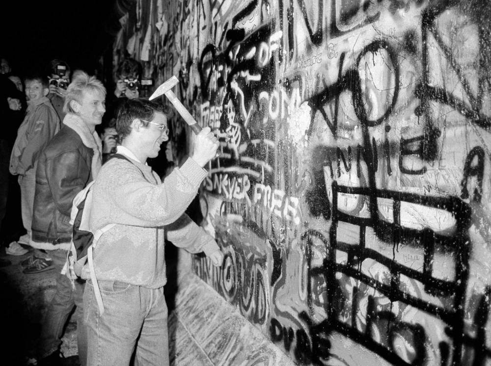 A man hammers a section of the Berlin Wall near the Brandenburg Gate after the opening of the East German border was announced in Berlin, in this file picture taken November 9, 1989. Germany will celebrate the 25th anniversary of the fall of the wall on November 9, 2014.    REUTERS/Fabrizio Bensch/Files (GERMANY - Tags: ANNIVERSARY CONFLICT POLITICS CIVIL UNREST)