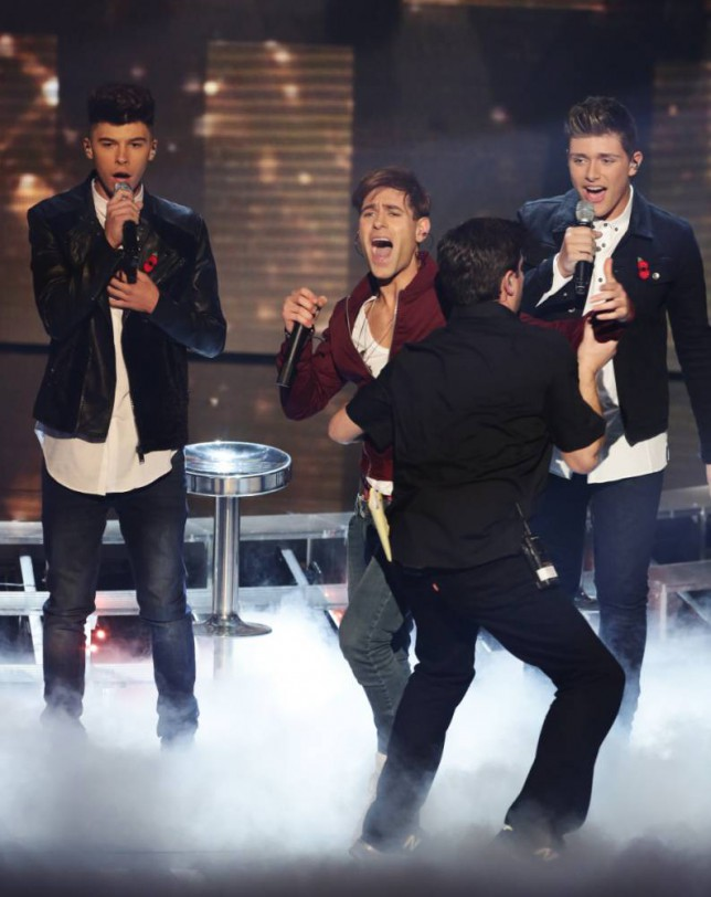 *** MANDATORY BYLINE TO READ: Syco / Thames / Corbis ***<BR/> A microphone wielding gatecrasher runs onto the stage during Stereo Kicks' live X Factor performance in London before security escorted him off the set. Jake Sims can be seen smiling as the mystery stage invader as he high-fived all the band, who carried on performing without interruption. <P> Pictured: Stereo Kicks and the stage invader <B>Ref: SPL885644  081114  </B><BR/> Picture by: Tom Dymond/Syco/Thames/Corbis<BR/> </P>