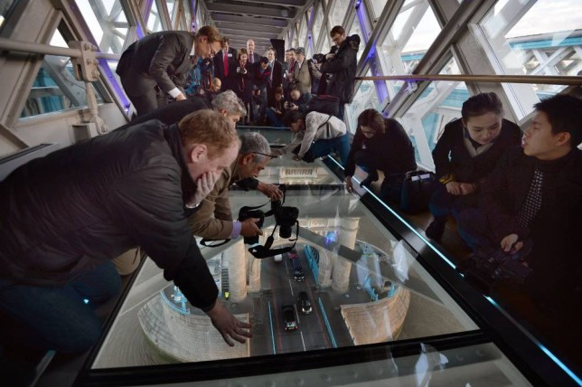 RETRANSMISSION REMOVING EMBARGO IN LIGHT OF NEW INFORMATION Members of the media capture the view from the newly installed glass floor 138 feet above the River Thames at Tower Bridge, London, after a £1 million improvement. PRESS ASSOCIATION Photo. Picture date: Monday November 10, 2014. The floor will allow visitors a view of the bridge lifts and is the most significant change since the Tower bridge Experience opening in 1982. See PA story TOURISM TowerBridge. Photo credit should read: John Stillwell/PA Wire