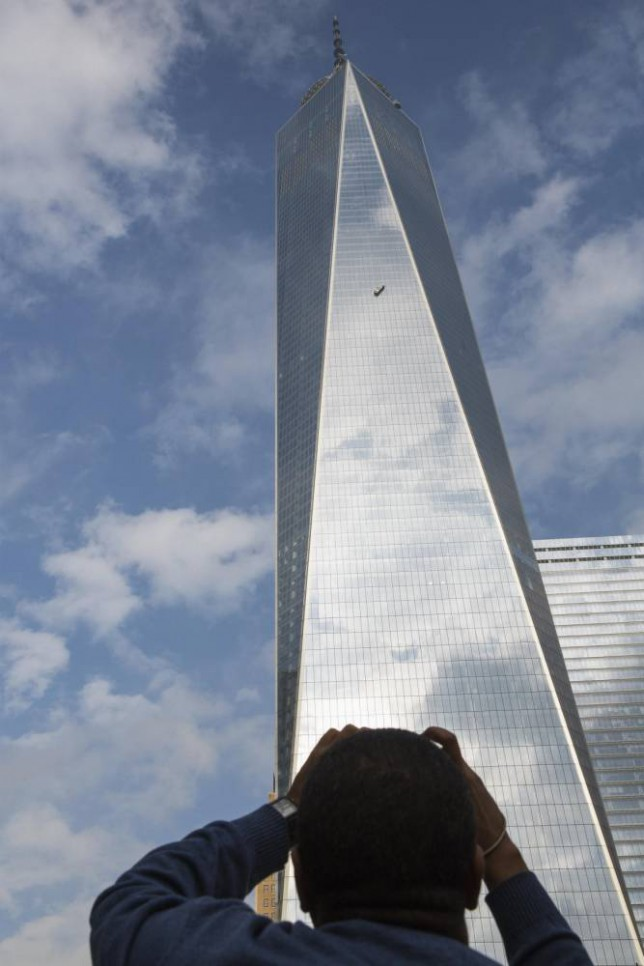 A man leans out of his car window to photograph stranded window washers hanging on the side of 1 World Trade Center in New York November 12, 2014. Two window washers caught on dangling scaffolding on the 69th floor of New York City's 1 World Trade Center were pulled to safety on Wednesday through a window cut in the tallest U.S. skyscraper, a building official said. REUTERS/Brendan McDermid (UNITED STATES - Tags: DISASTER)