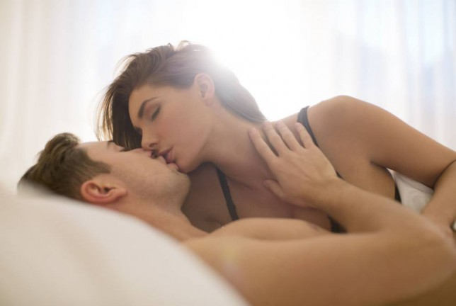 A couple kiss in a bed