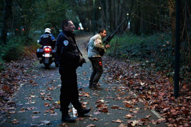Members of the police animal brigade walk through a wood in Montevrain, east of Paris, Thursday Nov. 13, 2014. French authorities say a young tiger is on the loose near Disneyland Paris, one of Europe's top tourist destinations, and have urged residents in three towns to stay indoors. (AP Photo/Thibault Camus)
