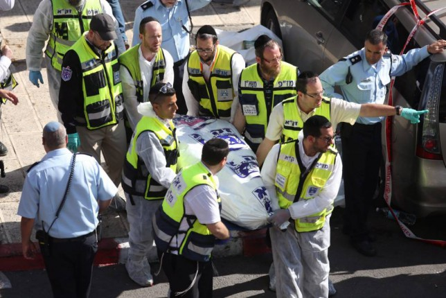 epaselect epa04493995 Emergency personel remove a dead body at the scene of an attack at a synagogue in a religious area of Jerusalem, 18 November 2014. Initial reports say at least two Palestinian men from East Jerusalem entered the synagogue with weapons and attacked worshippers, killing five Israelis and injuring some 10 others.  EPA/ABIR SULTAN