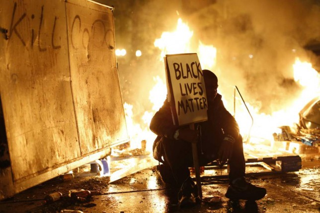 A demonstrator sits in front of a street fire during a demonstration following the grand jury decision in the Ferguson, Missouri shooting of Michael Brown, in Oakland, California November 25, 2014. The grand jury decided on Monday not to indict a white police officer over the fatal August shooting of an unarmed black teenager.  REUTERS/Stephen Lam  (UNITED STATES - Tags: CIVIL UNREST POLITICS CRIME LAW TPX IMAGES OF THE DAY)