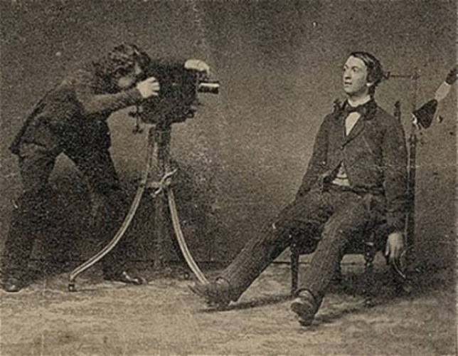 A photographer takes a post-mortem picture of a dead man