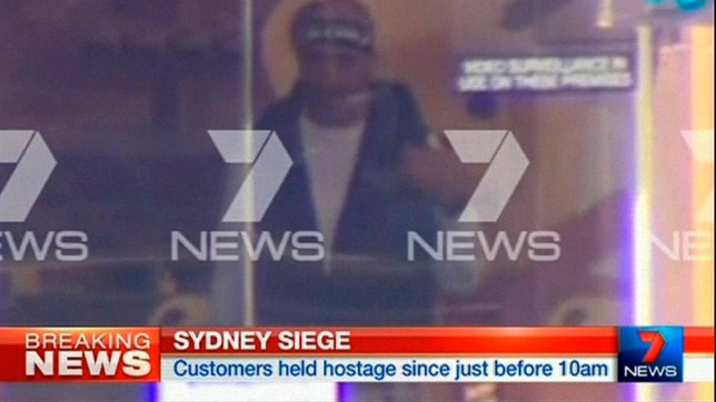This image taken from video shows a man believed to be a gunman inside a cafe in Sydney, Australia Monday, Dec. 15, 2014. An apparent hostage situation was unfolding inside the chocolate shop and cafe in Australia's largest city on Monday, where several people could be seen through a window with their hands held in the air. (AP Photo/Channel 7 via AP Video) AUSTRALIA OUT