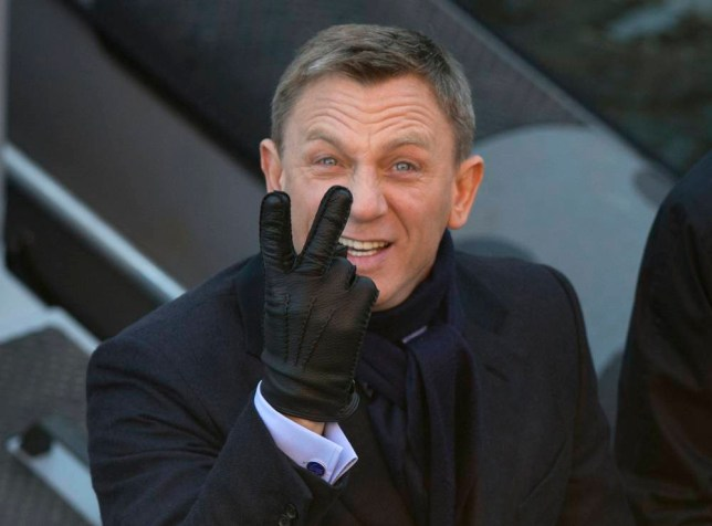 Actors Daniel Craig jokingly gestures to photographers as he films a scene for the new James Bond film, Spectre, in London, Tuesday, Dec. 16, 2014. (AP Photo/Alastair Grant)