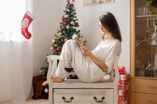 Woman reads a book and enjoys a glass of wine alone at Christmas