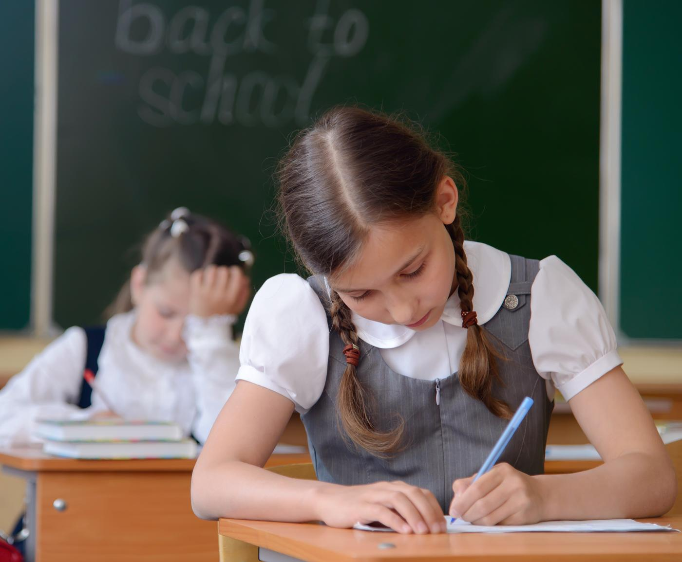 Two schoolgirls sitting in class and writing against blackboard with 'back to school' on background. IMAGE FOR RF ONLY - This image has been previously licensed for Royalty Free Kolett/Kolett