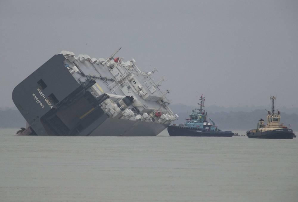 The cargo ship Hoegh Osaka lies on its side after being deliberately ran aground on the Bramble Bank in the Solent estuary, near Southampton in southern England January 5, 2015. The vessel was deliberately run aground on Saturday evening after it began to list, according to its owners Hoegh Autoliners.  REUTERS/Peter Nicholls (REUTERS - Tags: TRANSPORT DISASTER ENVIRONMENT)