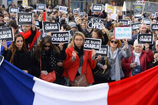 """People hold placards reading in French """"I am Charlie"""" behind a french flag during a public show of solidarity at Plaza del Sol in Madrid on January 11, 2015 and to protest against three days of bloodshed triggered by an attack on French satirical weekly Charlie Hebdo that left 12 dead.  More than a million people and dozens of world leaders are expected to participate in a massive and historic march in Paris today in solidarity with the victims of the Islamist attacks that killed 17 and deeply shook the country.  AFP PHOTO / GERARD JULIENGERARD JULIEN,GERARD JULIEN/AFP/Getty Images"""