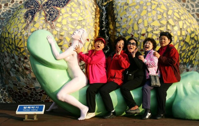 "JEJU, SOUTH KOREA - OCTOBER 24:  People visit the theme park 'Love Land' on October 24, 2009 in Jeju, South Korea. Love Land is an outdoor sex-themed sculpture park which opened in 2004 on Jeju Island. The park runs sex education films and features 140 sculptures representing humans in various sexual positions. It also has other elements such as large phallus statues, stone labia, and hands-on exhibits such as a ""masturbation-cycle.""  (Photo by Chung Sung-Jun/Getty Images)"