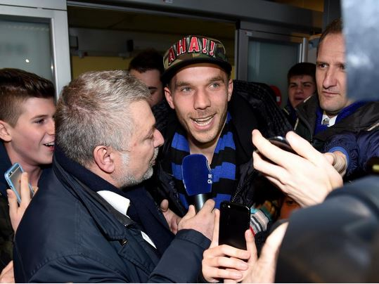 Arsenal's Lukas Podolski mobbed by fans after arriving in Italy to finalise Inter Milan loan transfer