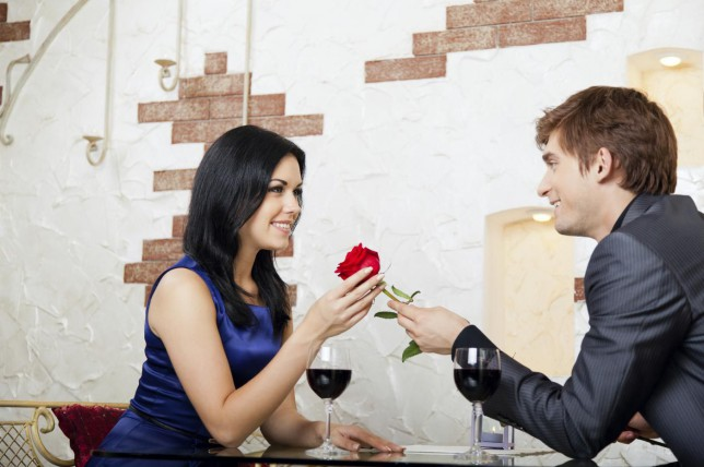 Young happy couple romantic date at restaurant, celebrating valentine day man give red rose to his girl gmast3r/gmast3r