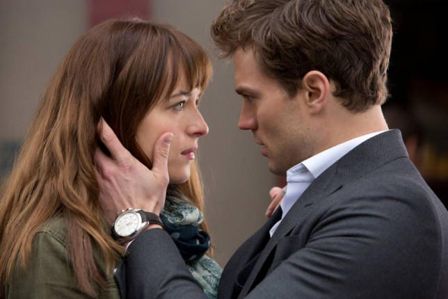 """In this image released by Universal Pictures and Focus Features, Dakota Johnson, left, and Jamie Dornan appear in a scene from the film, """"Fifty Shades of Grey.""""  (AP Photo/Universal Pictures and Focus Features)"""