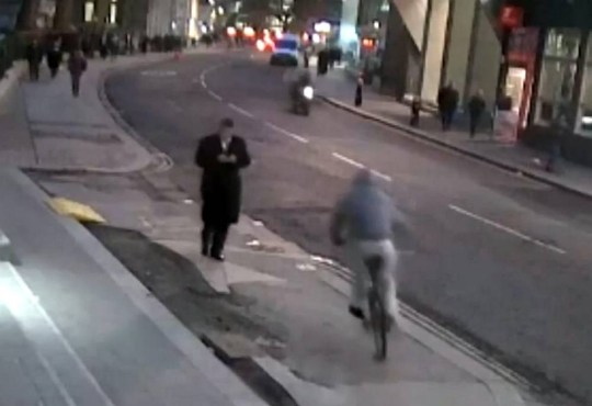 """This is the split-second moment a pedestrian had his mobile phone snatched out of his hand ñ by a man racing past on a BIKE.  See SWNS story SWSNATCH.  The 41-year-old victim was walking along the pavement and using his mobile when it was torn from his hands in a millisecond by a passing cyclist ñ who then sped off down the street.  The incident, which was captured on CCTV, happened at around 5pm on January 26, in central London, and the sucpect is described as a white male, who was wearing a grey hoodie and white tracksuit bottoms.  City of London Police Inspector Doug Blackwood said, """"We advise the public to be vigilant when using their phone out and about on the street in London.î"""
