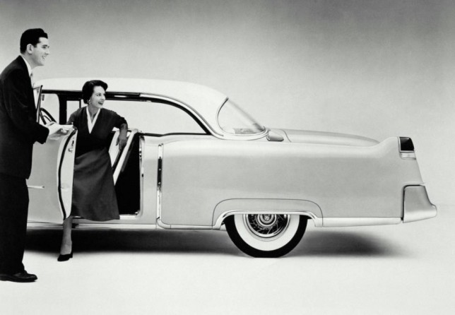 1950s picture of a man opening a car door for a woman