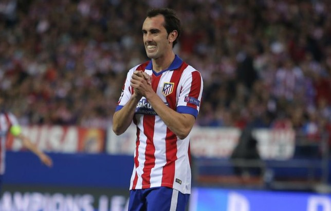 Atletico's Diego Godin reacts next to Real Madrid's Sergio Ramos, right, during the Champions League quarterfinal first leg soccer match between Atletico Madrid and Real Madrid at the Vicente Calderon stadium in Madrid, Spain, Tuesday, April 14, 2015. (AP Photo/Andres Kudacki) AP Photo/Andres Kudacki