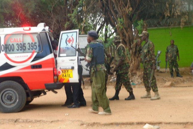 GARISSA, KENYA - APRIL 2: Policemen help one of the people injured in an attack at Garissa University College into an ambulance on April 2, 2015, in Garissa, Kenya. Masked gunmen stormed a university in Garissa, northeast Kenya, in the early hours of Thursday (March 2) morning, leaving at least two dead and many more injuries. The Somalia-based militant group al-Shabaab have claimed responsibility for the attack at Garissa University College, which saw the gunmen reportedly set off a blast at the gates of the university's student hostels, before storming the compound and taking hostages.  PHOTOGRAPH BY Abdimalik Hajir / Nation Media Group / Barcroft Media UK Office, London. T +44 845 370 2233 W www.barcroftmedia.com USA Office, New York City. T +1 212 796 2458 W www.barcroftusa.com Indian Office, Delhi. T +91 11 4053 2429 W www.barcroftindia.com
