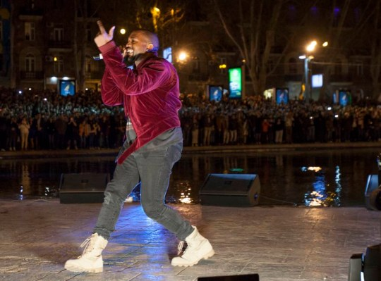 Kanye West performs an impromptu gig near Swan Lake in Yerevan, Armenia, Sunday, April 12, 2015. The Kardashian sisters, along with Kim's husband Kanye West and their daughter North are on a visit to their ancestral Armenia. The concert was halted by police after the singer jumped into a lake, prompting hundreds of fans to jump in after him. (AP Photo/PAN Photo / Vahan Stepanyan)