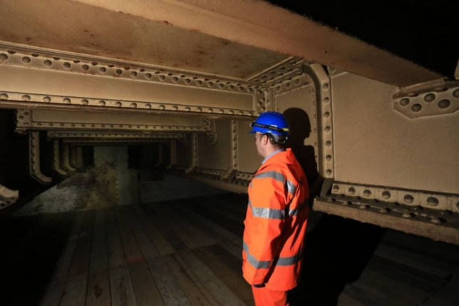 """Undated handout photo issued by Network Rail of Greg Thornett, Project Manager, looking at the remains of Southwark Park station, a """"ghost"""" station that closed a century ago, which has been uncovered during work on a £6.5 billion rail project. PRESS ASSOCIATION Photo. Issue date: Monday April 20, 2015. Southwark Park station in south London only served passengers from 1902 to 1915 before shutting for good. But now engineers constructing the Bermondsey Dive Under as part of the Thameslink Programme have rediscovered the former ticket hall and platforms. See PA story RAIL Ghost. Photo credit should read: Network Rail/PA Wire NOTE TO EDITORS: This handout photo may only be used in for editorial reporting purposes for the contemporaneous illustration of events, things or the people in the image or facts mentioned in the caption. Reuse of the picture may require further permission from the copyright holder."""