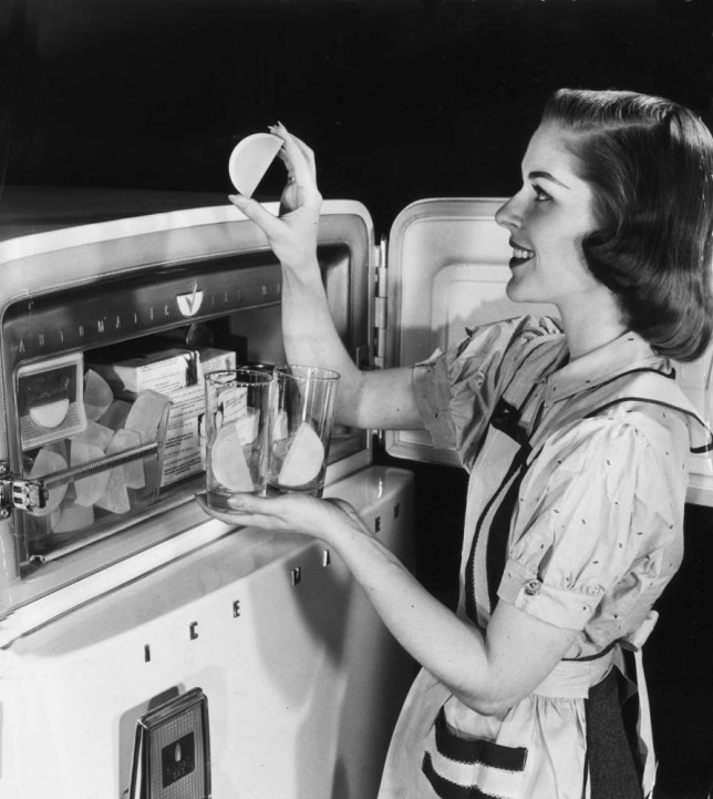 circa 1945: A housewife smiles as she stands at her freezer, removing half-moon shaped ice cubes from an automatic ice maker, and putting them in glasses. (Photo by Hulton Archive/Getty Images)
